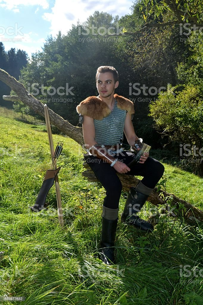 Medieval archer  on branch with drinking horn ,arrow and curve stock photo