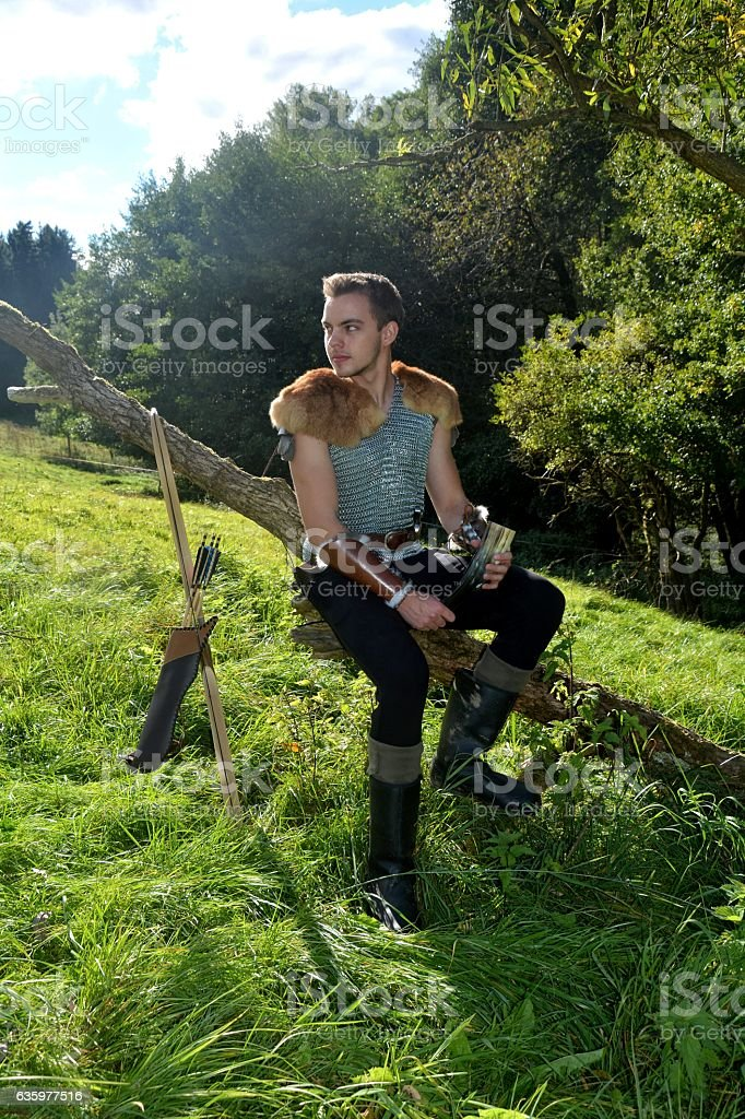 Medieval archer   on branch with drinking horn ,bow and arrow stock photo