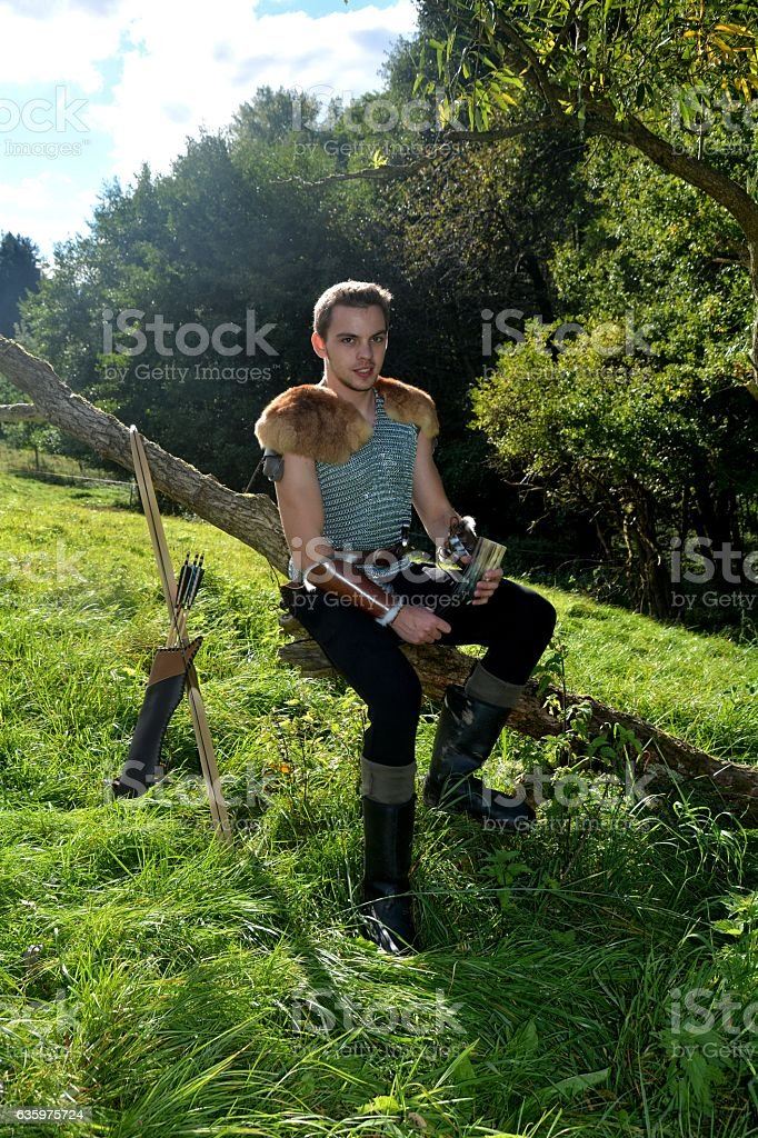 Medieval archer  sits on branch , arrow and curve stands besides stock photo