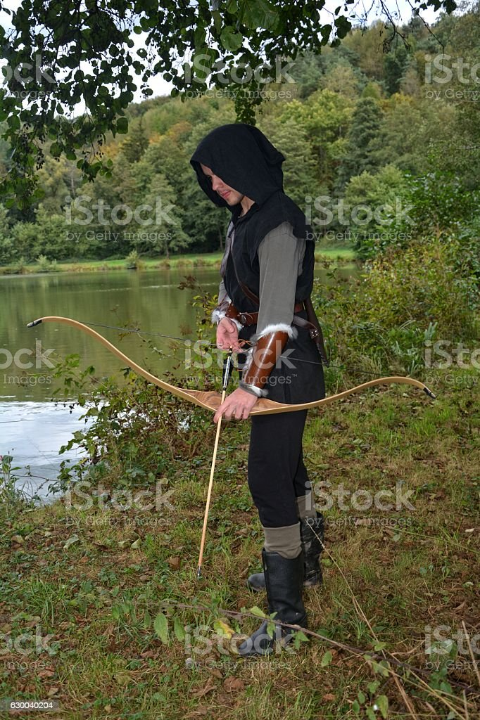 Medieval archer stands with tense curve and with arrows stock photo