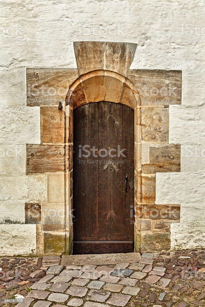 Medieval building with brown wooden door framed by sandstones stock photo