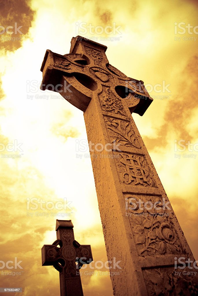 Medieval Celtic Cross with sunset colors in Irish cemetery stock photo