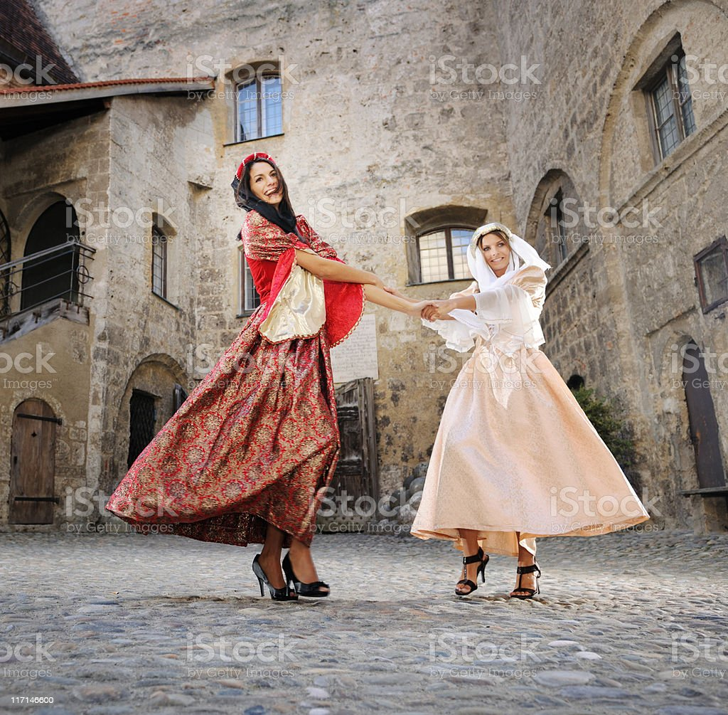 Medieval Damsels dancing in a historical Court Yard royalty-free stock photo