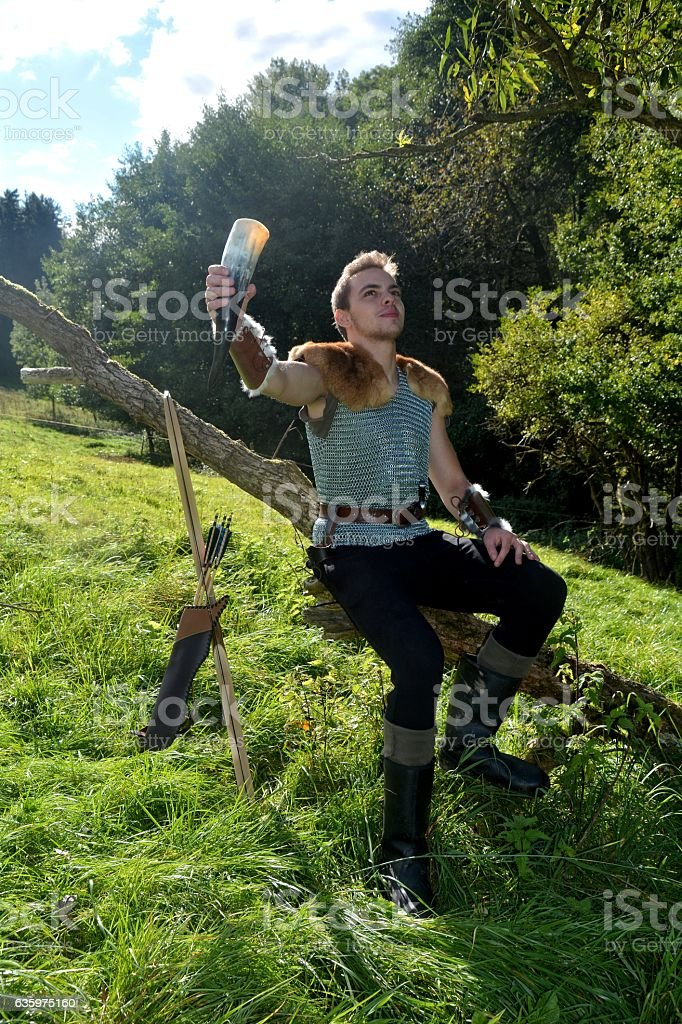 Medieval dressed man, holds drinking horn high in the hand stock photo