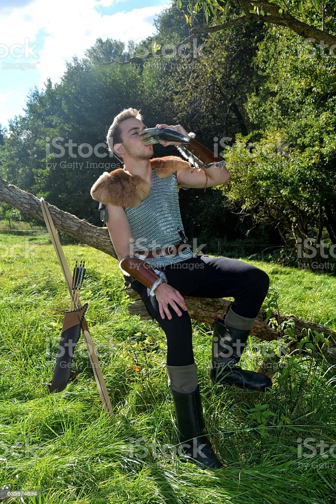 Medieval dressed man, sits on branch, drinks from drinking horn stock photo
