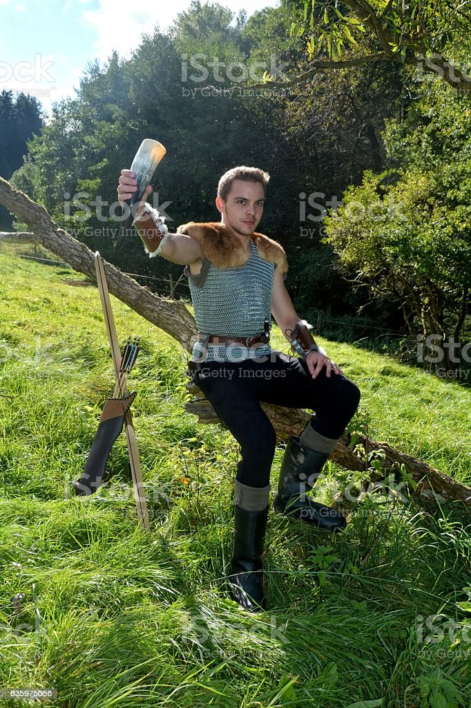Medieval dressed one man, holds drinking horn high in hand stock photo