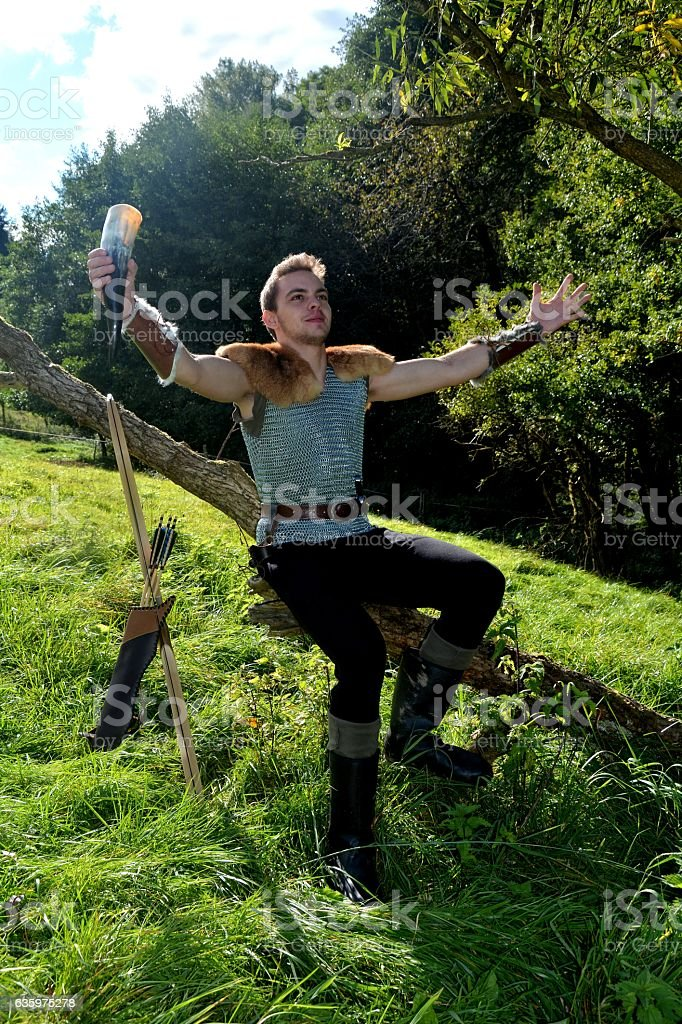 Medieval dressed one  man, with  drinking horn ,  arms stretched out stock photo