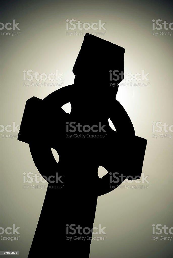 Medieval Irish Celtic Cross silhouette with sun behind stock photo