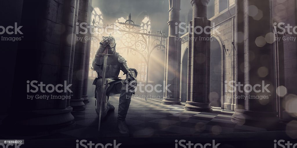 Medieval Knight in Armour Kneeling With Sword Inside Castle stock photo