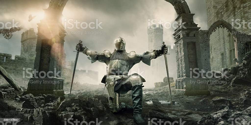 Medieval Knight Kneeling With Sword In Front of Building Ruin stock photo