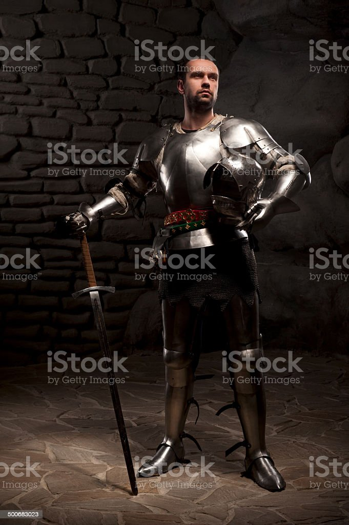 Medieval Knight posing with sword in a dark stone background stock photo