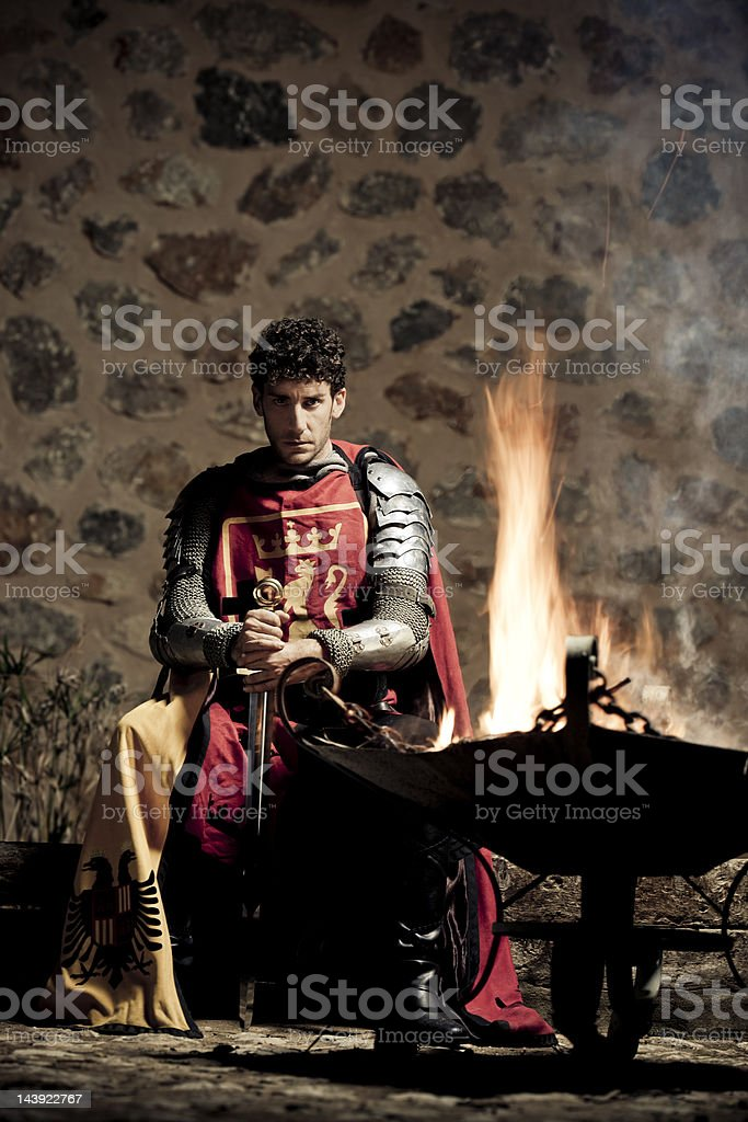 Medieval Knight sitting in the darkness closed to fire stock photo