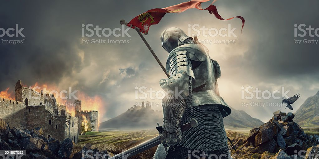Medieval Knight With Banner and Sword Standing Near Burning Castle stock photo