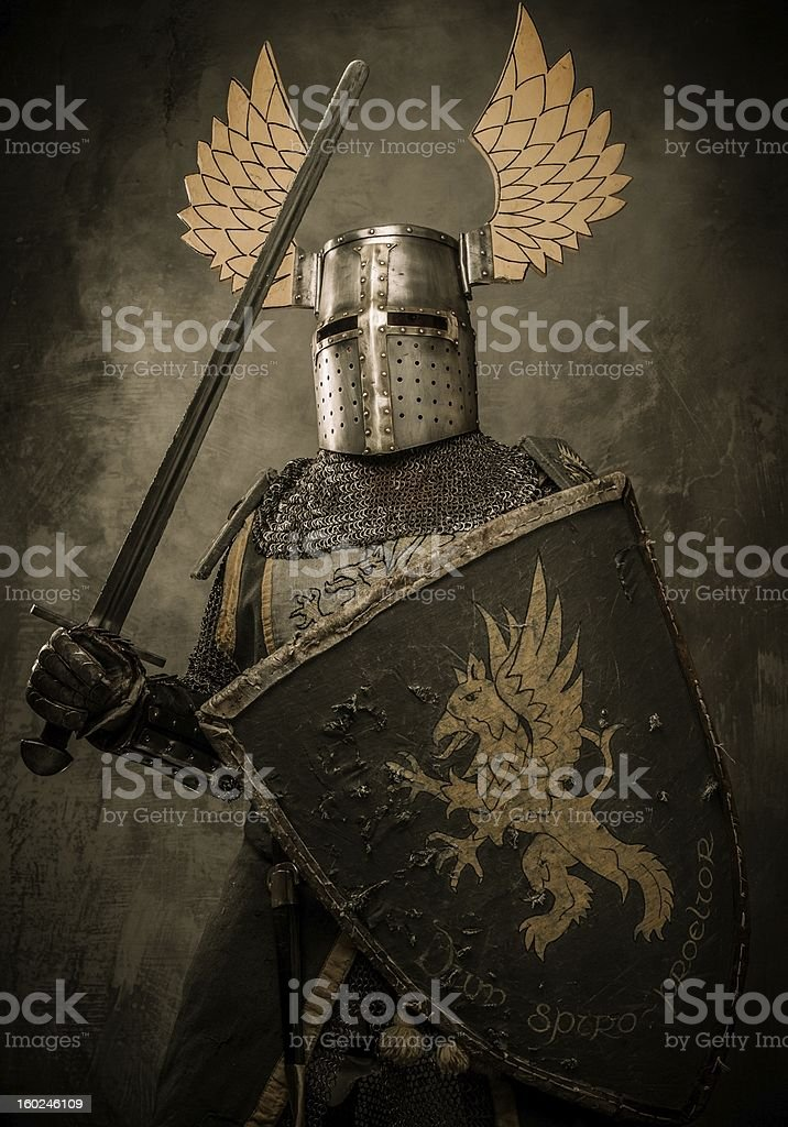 Medieval knight with sword and shield against stone wall royalty-free stock photo