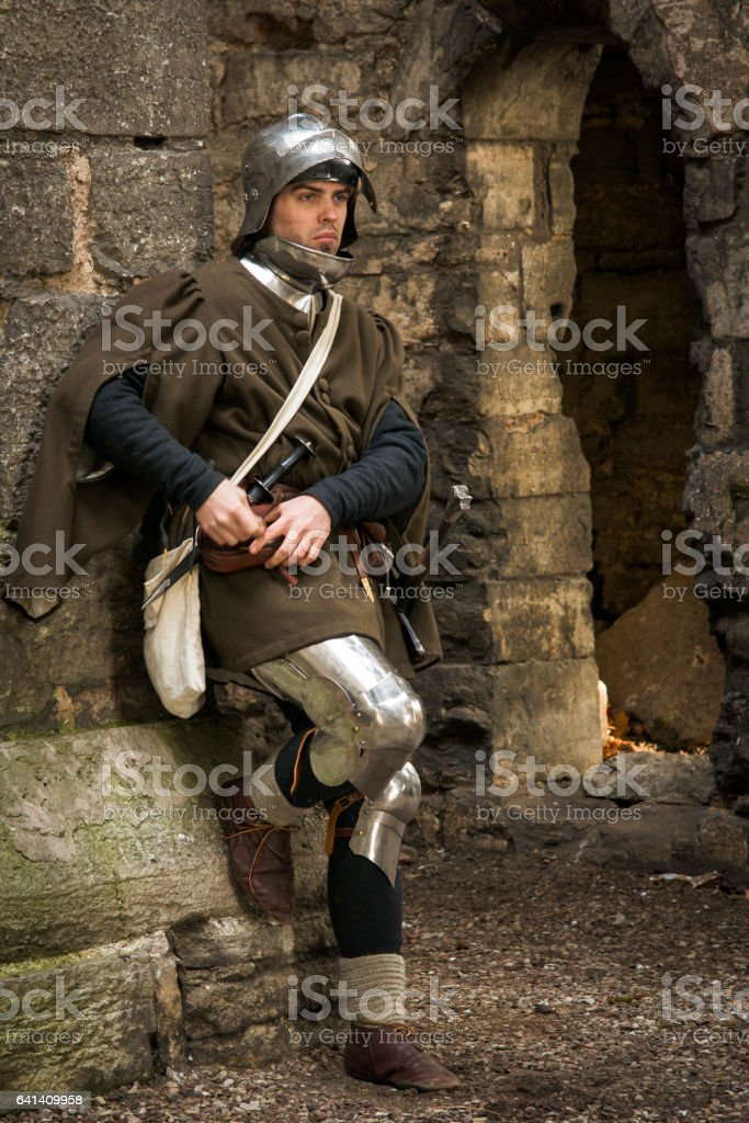Medieval man in armor rests stock photo