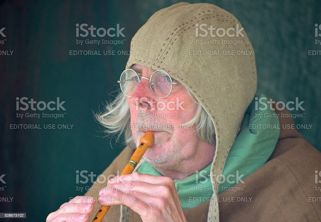 Medieval musician or minstrel playing whistle. stock photo