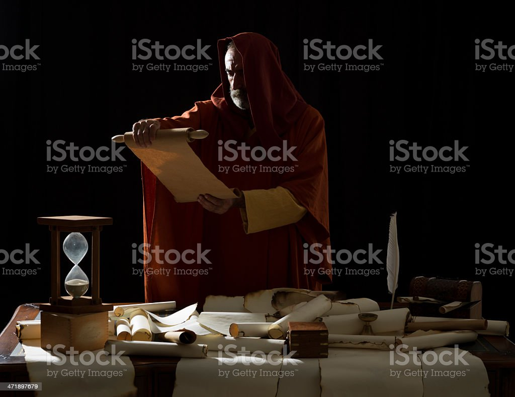 Medieval philosopher reading scrolls in dark stock photo