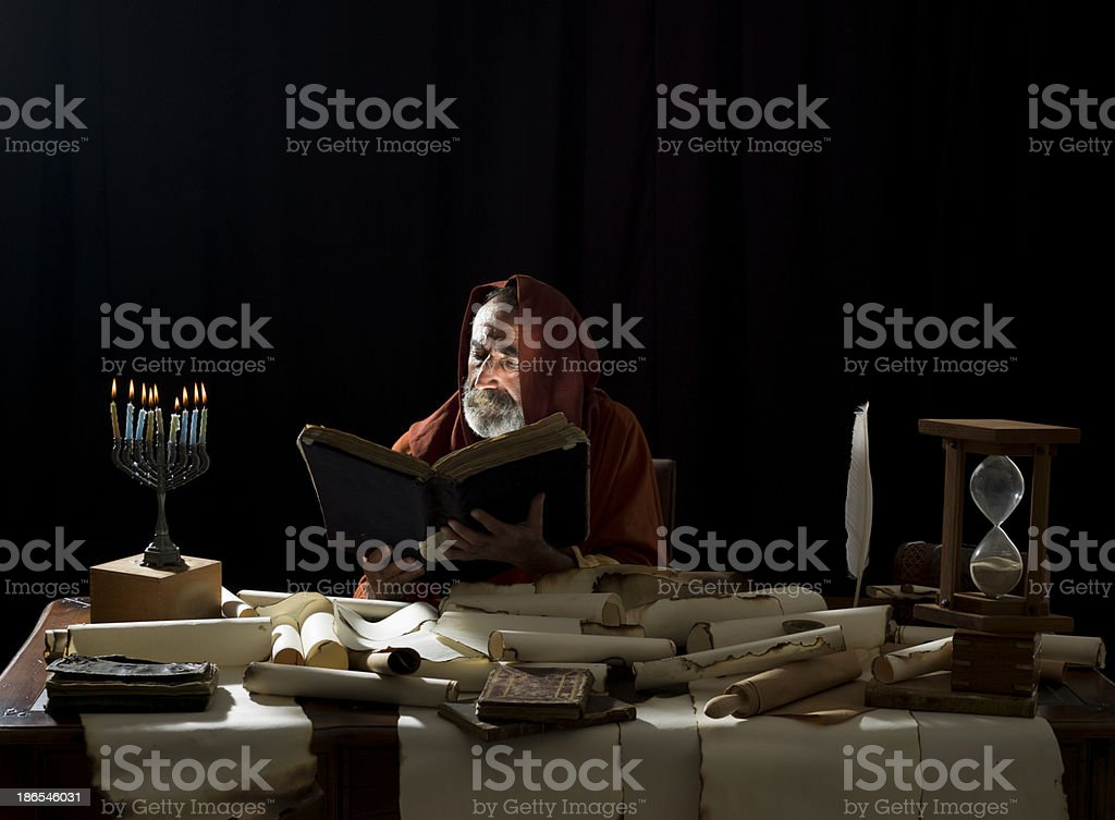 Medieval philosopher reading Torah in the light of menorah stock photo