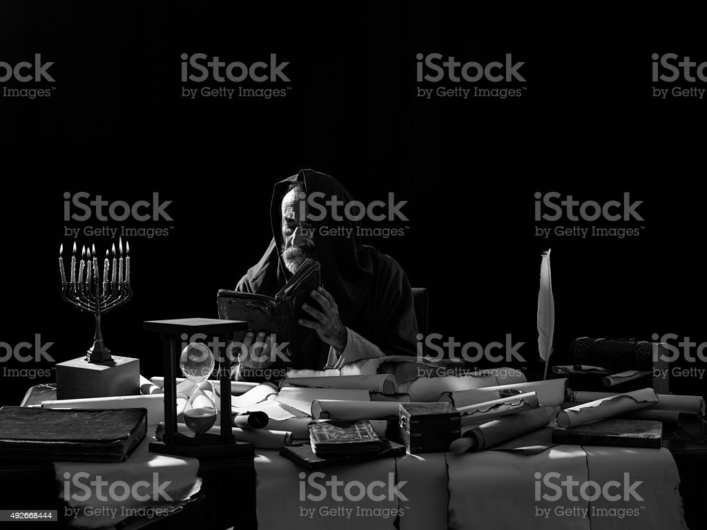 Medieval philosopher reading Torah under the light of menorah stock photo