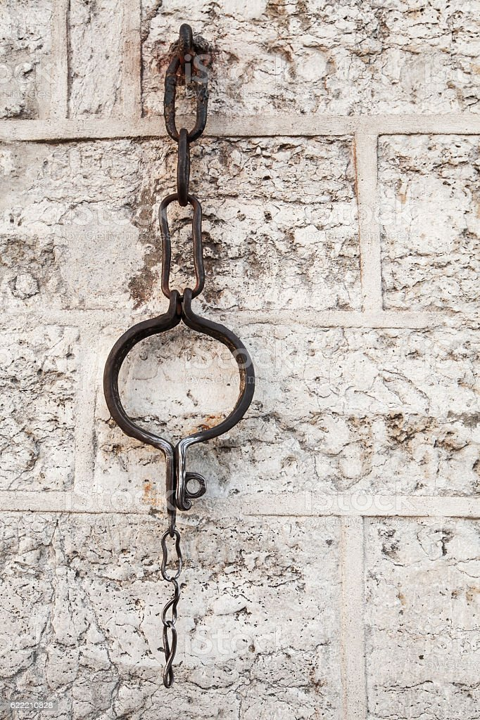 Medieval shackles mounted in old wall stock photo