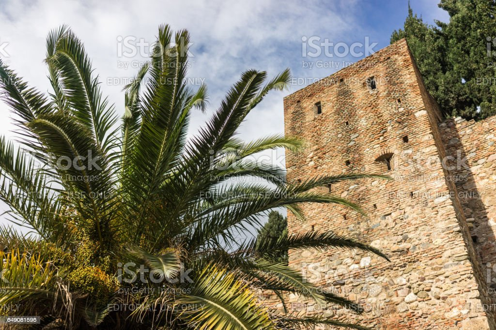 Medieval stone arches and walkway by the walls and towers of an ancient Alcazaba fortress stock photo