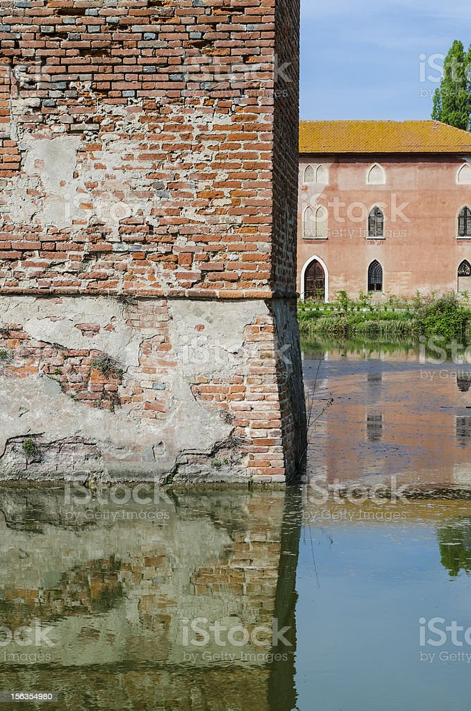 medieval tower, windows and trees reflected in water royalty-free stock photo