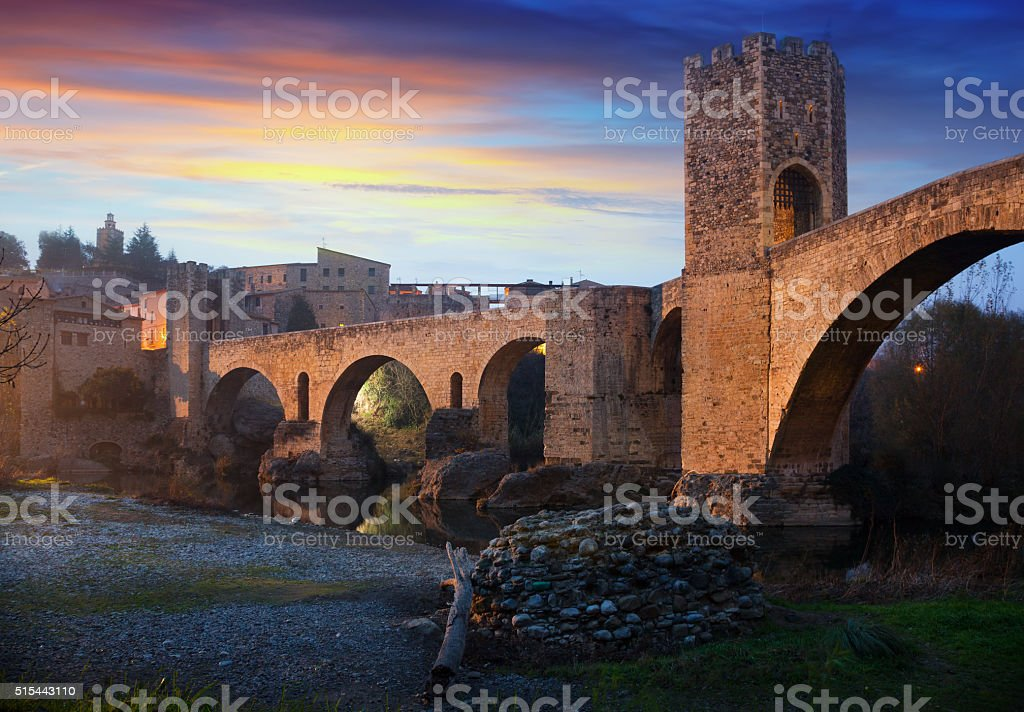 Medieval town with gate on bridge in evening. Besalu stock photo