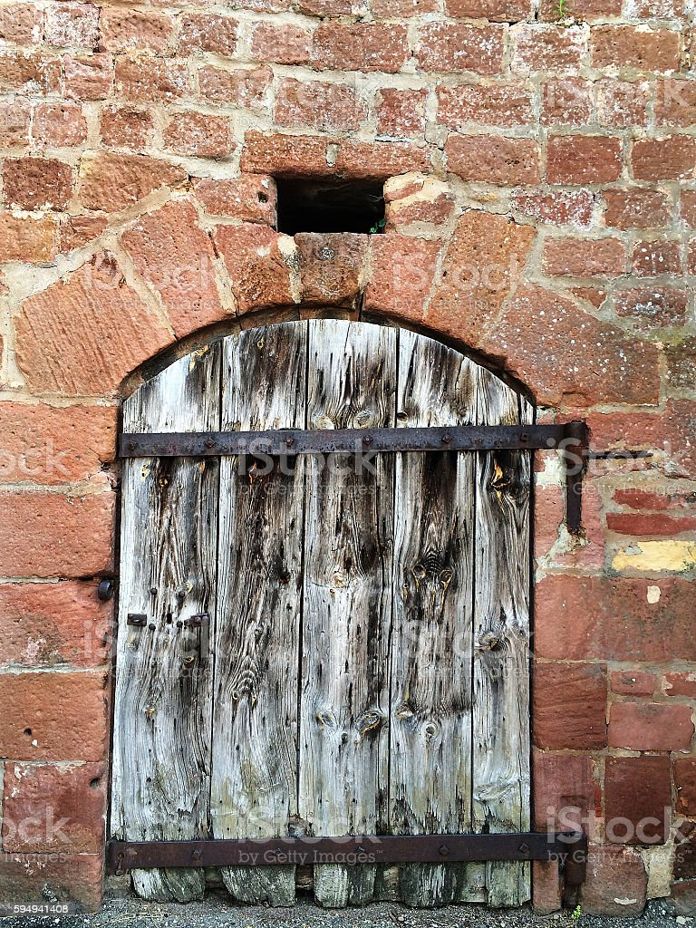 Medieval wall with wooden door stock photo