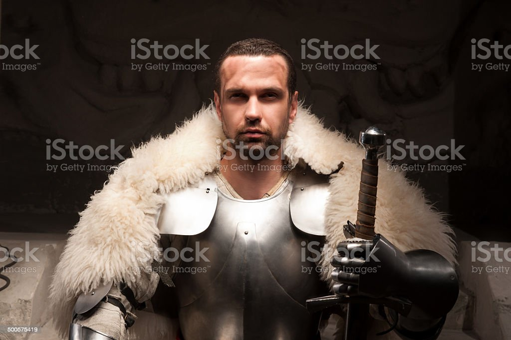 Medieval warrior in armor and fur mantle stock photo