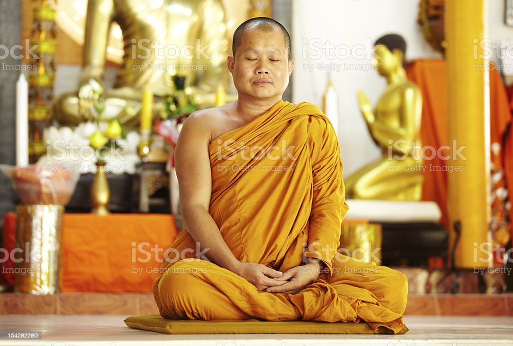 Meditating monk in a sacred shrine stock photo