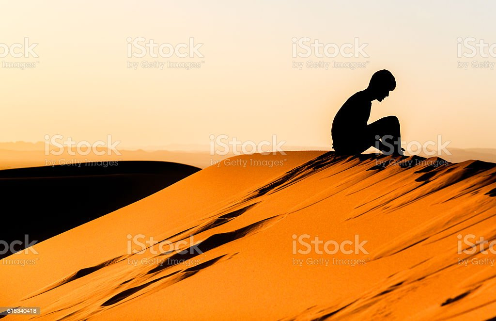 meditating of young man sitting on dune of sahara stock photo