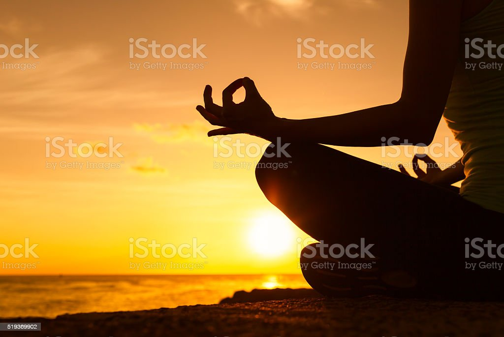 Meditating on the beach stock photo