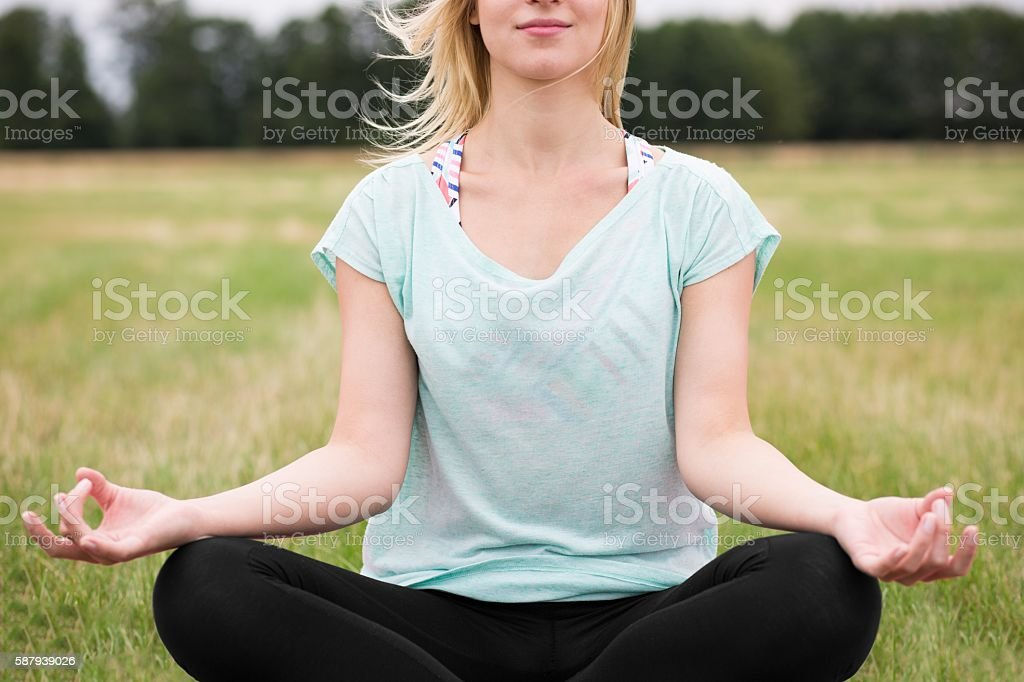 Meditating outside with legs crossed stock photo