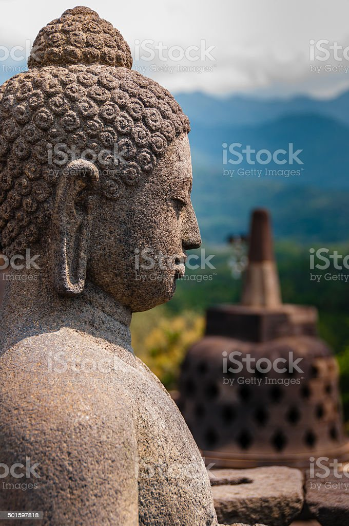 Meditating sitting Buddha sculputre sideview in stone at Borobudur stock photo