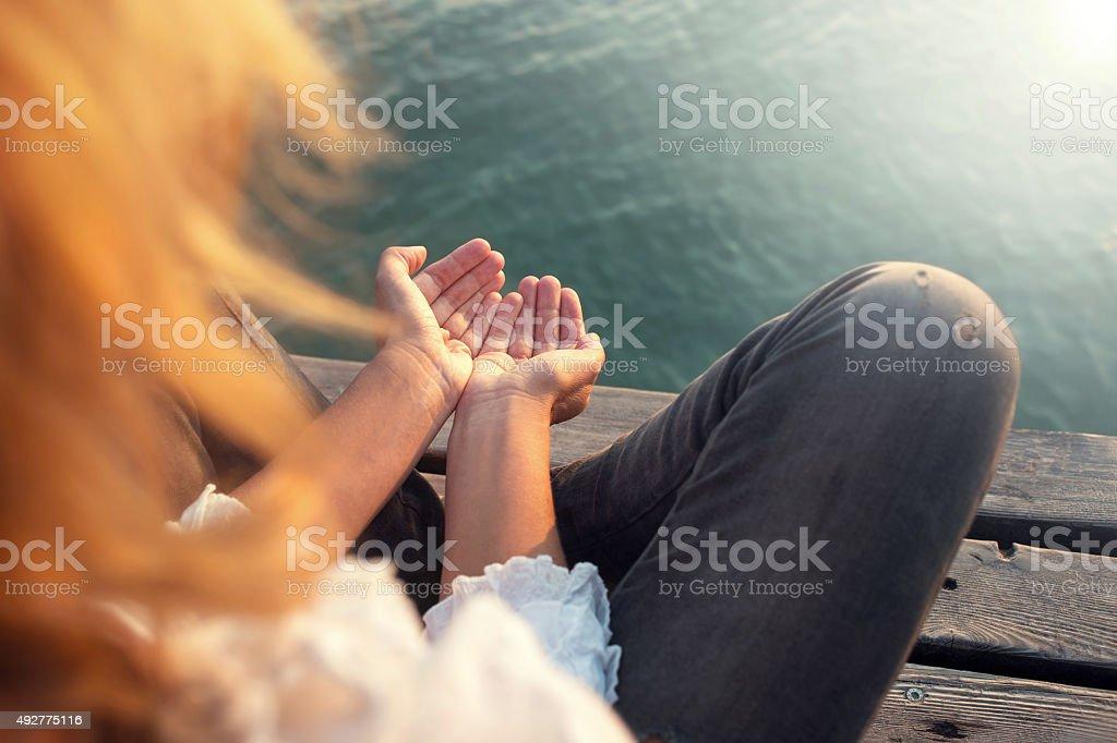 Meditation hand gesture on a boardwalk stock photo