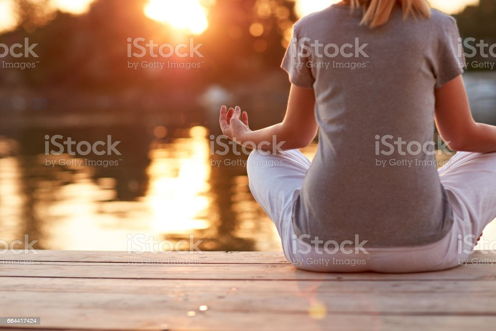 Meditation in yoga position near river - back view stock photo