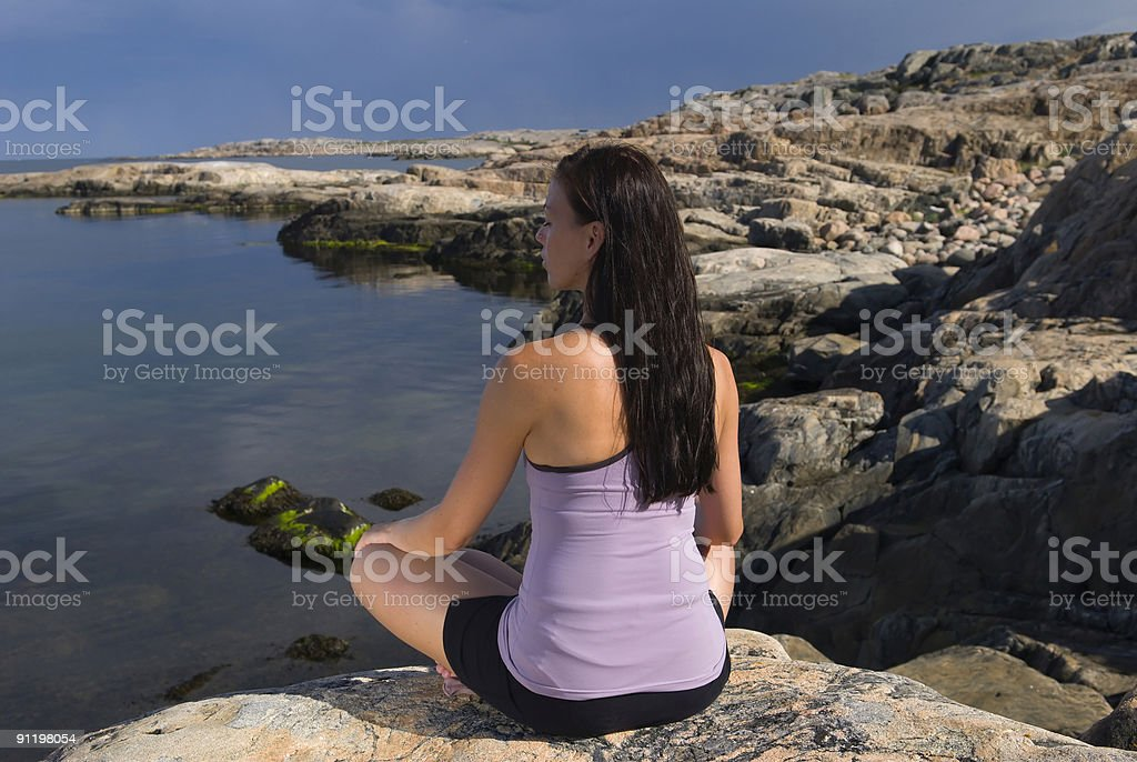 Meditation on a rock by the sea royalty-free stock photo