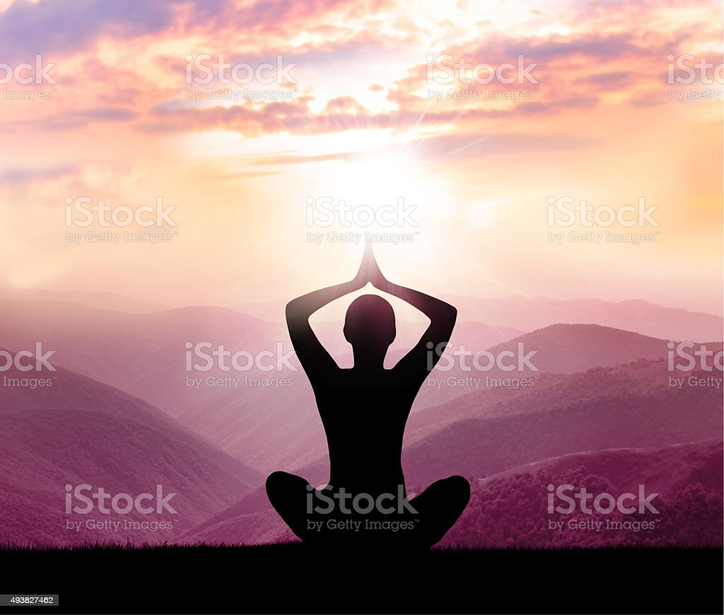Meditation. Silhouette of man in the mountain stock photo