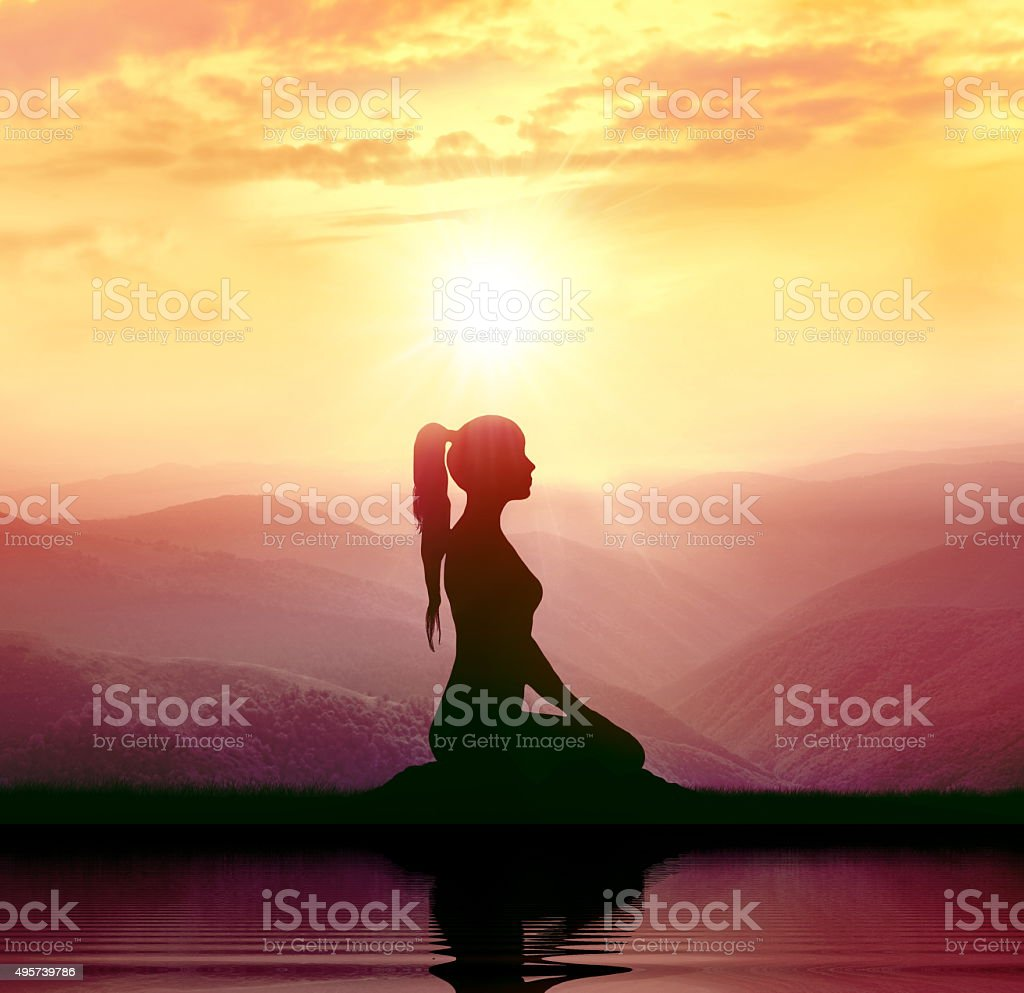 Meditation. Silhouette of woman in the mountain stock photo