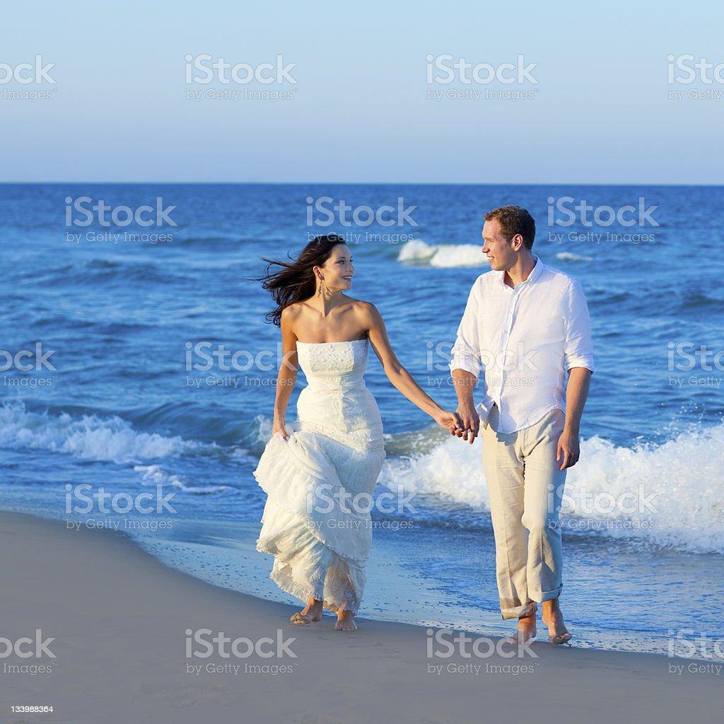 Mediterranean couple walking in blue beach royalty-free stock photo