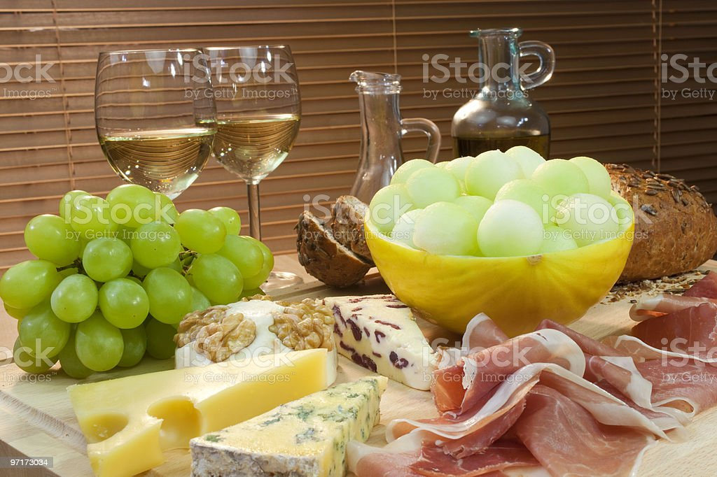 Mediterranean Diet of Cheese, Wine, Grapes, Bread Parma Ham & Melon royalty-free stock photo