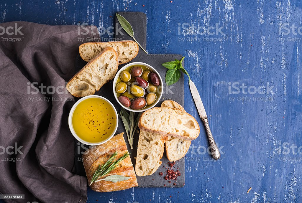 Mediterranean snacks set. Olives, oil, herbs and sliced ciabatta bread stock photo