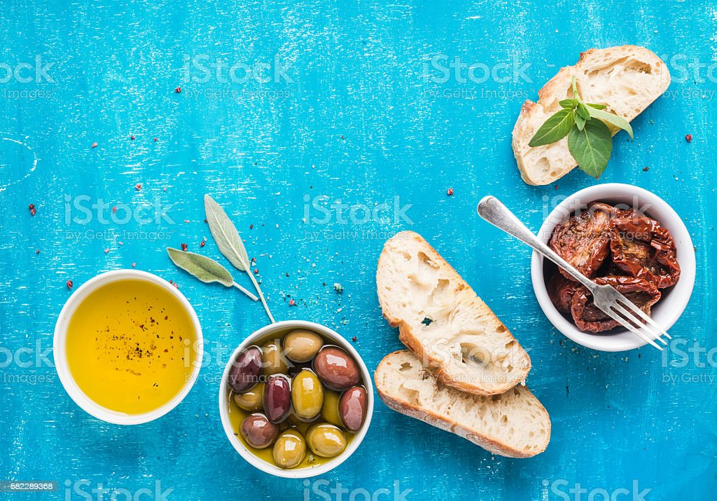 Mediterranean snacks set. Olives, oil, sun-dried tomatoes, herbs and stock photo
