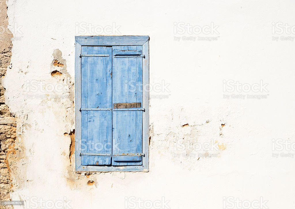 Mediterranean style old window. Blue on light wall with closed stock photo