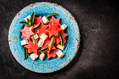 Mediterranean watermelon, feta cheese and mint salad on blue plate.
