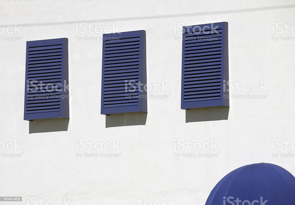 Mediterranean White Plaster Wall with Blue Shutters and Awnings royalty-free stock photo