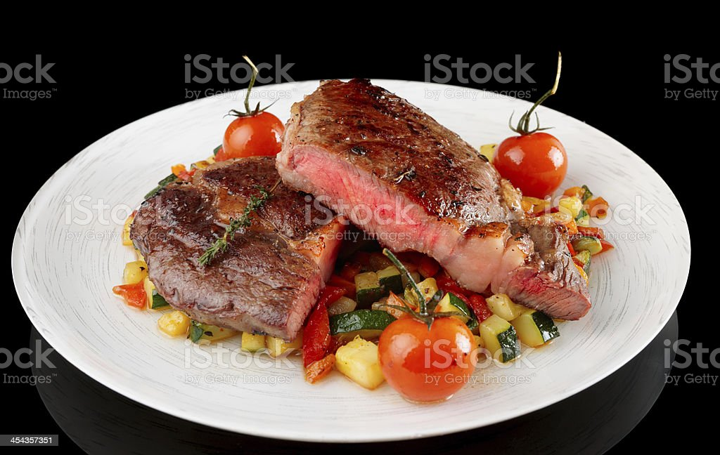 Medium fried steak with vegetables on black background royalty-free stock photo