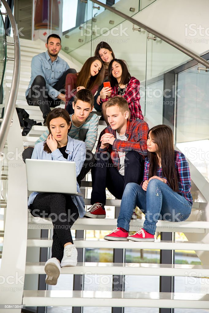 Medium group of students studying on steps of school building stock photo