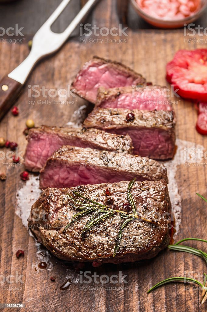 Medium rare roasted beef steak slices rustic wooden background stock photo