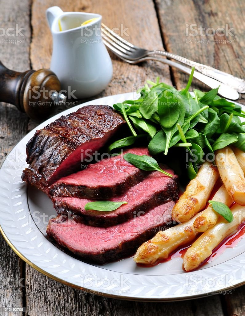 Medium rare steak with asparagus and baby spinach. stock photo